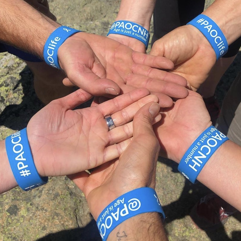 group of hands together wearing event wristbands